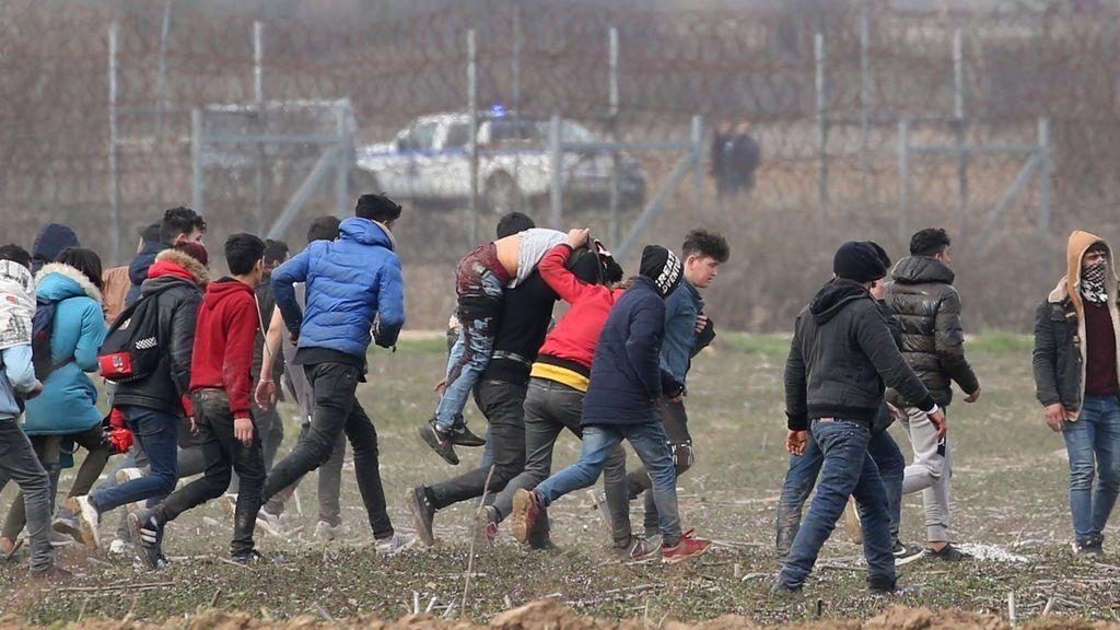Migrantes trasladan a un hombre herido y huyen del gas lacrimógeno en la frontera de Grecia y Turquía