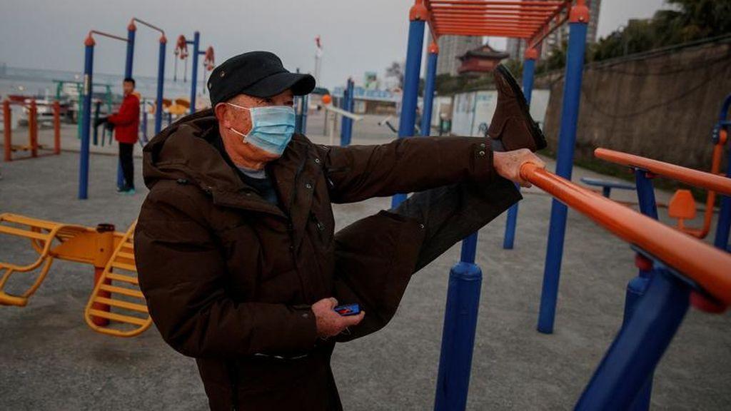 Un hombre con mascarilla realiza ejercicio físico en Jiujiang, China