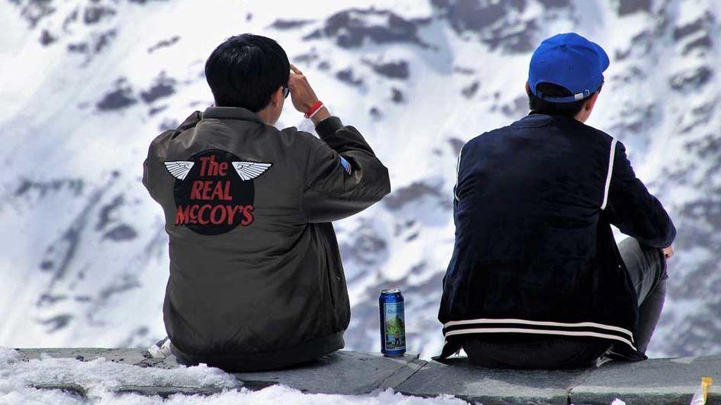 Dos turistas comparten cerveza en la nieve