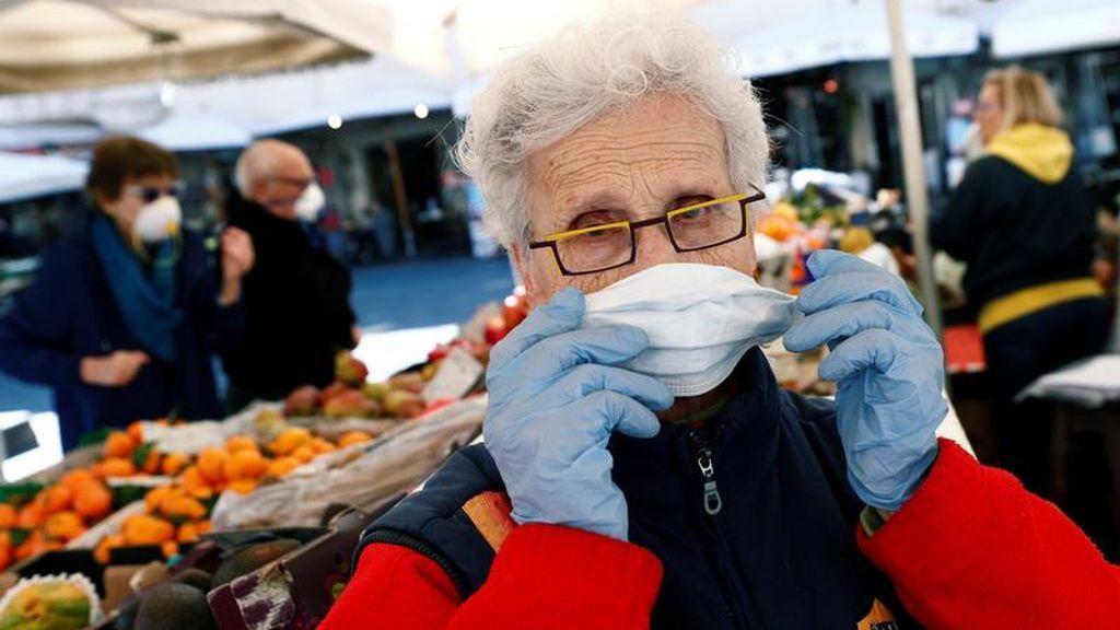 Una mujer usa mascarilla en un mercado italiano