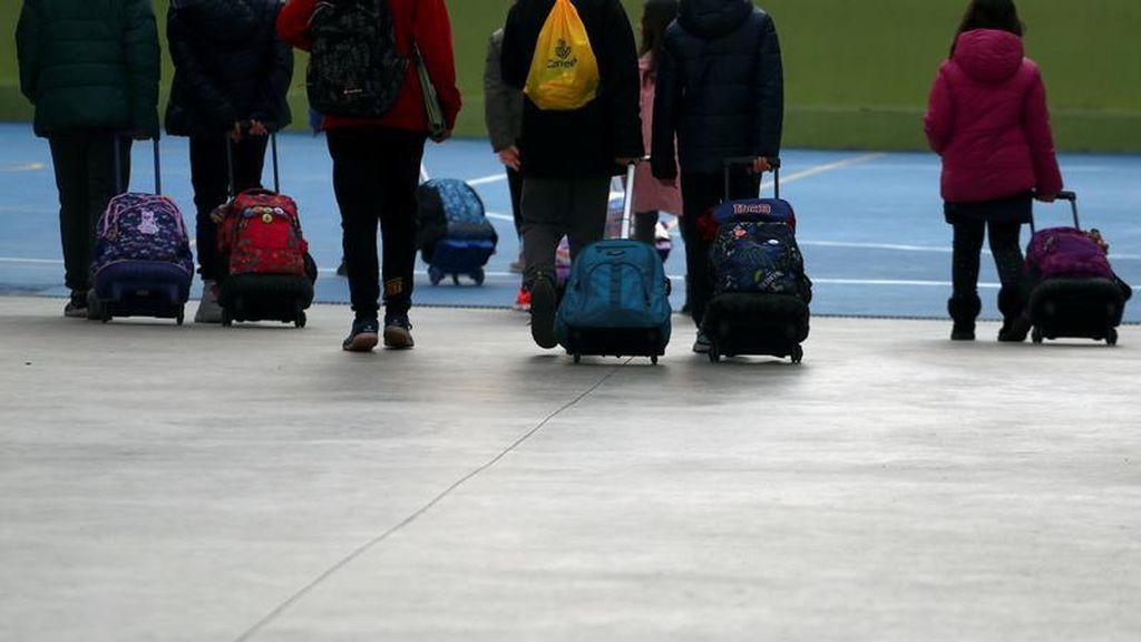 Un grupo de escolares camina con sus mochilas