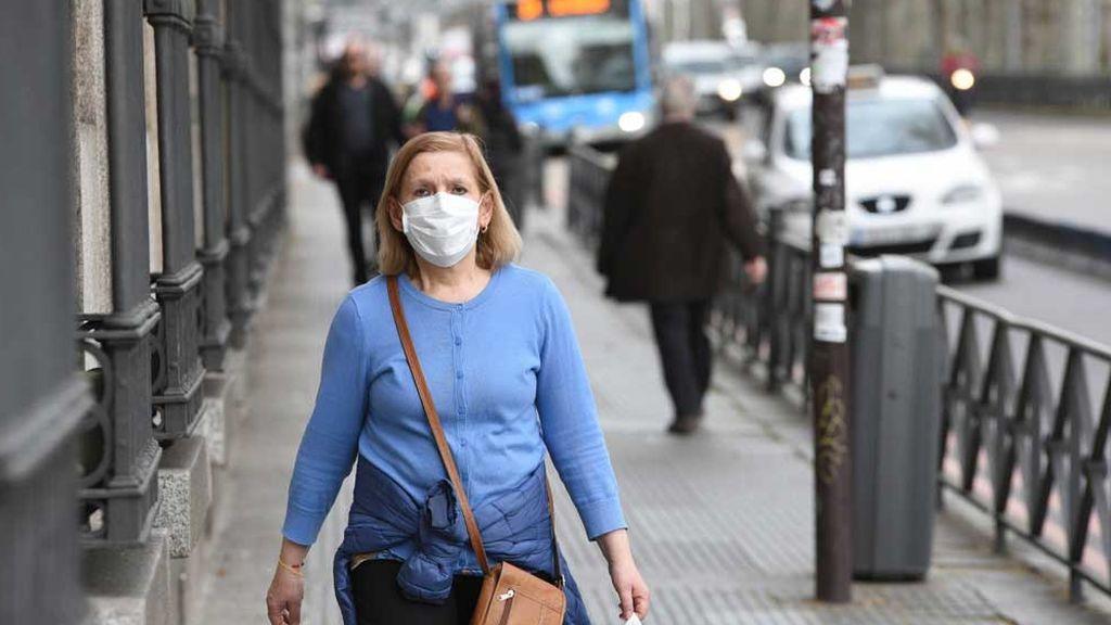 Señora con mascarilla pasea por el Paseo de Recoletos (Madrid)