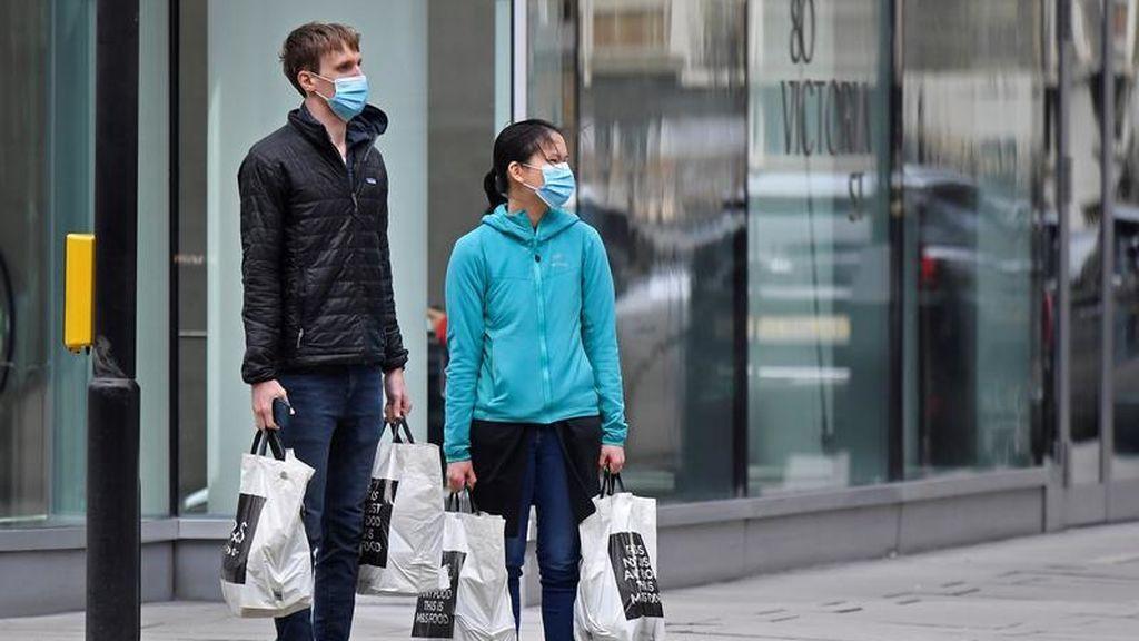 Una pareja sale de la compra con mascarillas