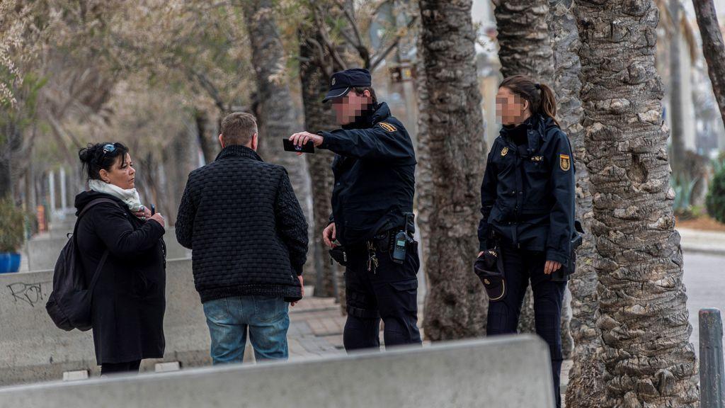 Agentes de la Policía indican a una pareja que deben regresar a su domicilio