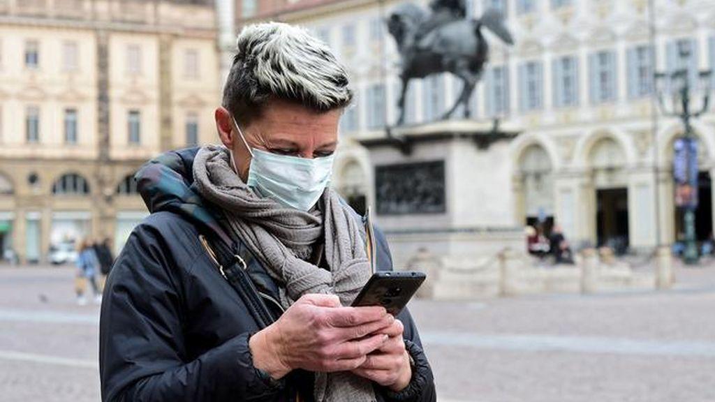 Una mujer sonríe tras la mascarilla mirando su móvil