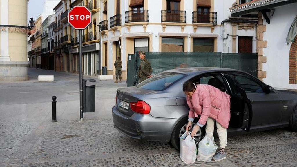 Una mujer coge las bolsas de la compra