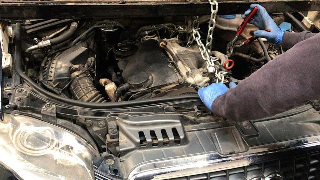 Un mecánico protegido con guantes arregla un motor