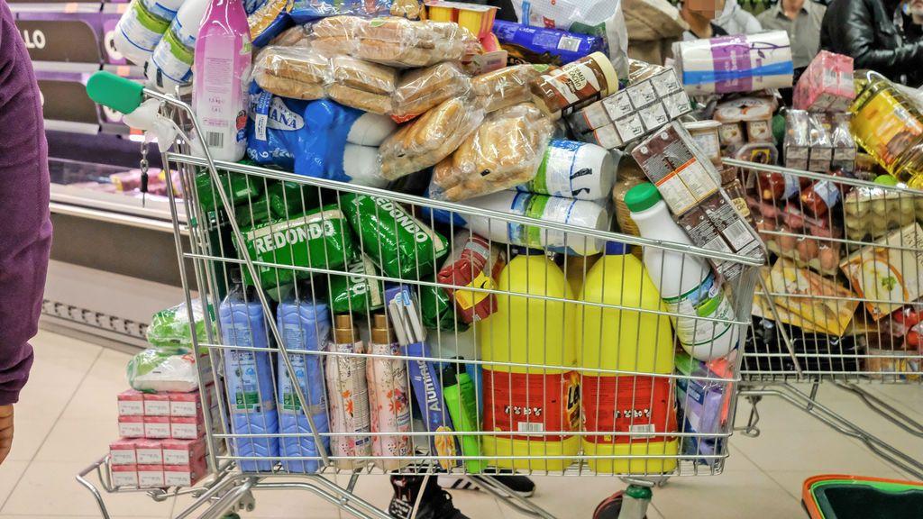 Un carro de supermercado a rebosar con varios productos de limpieza para el hogar.