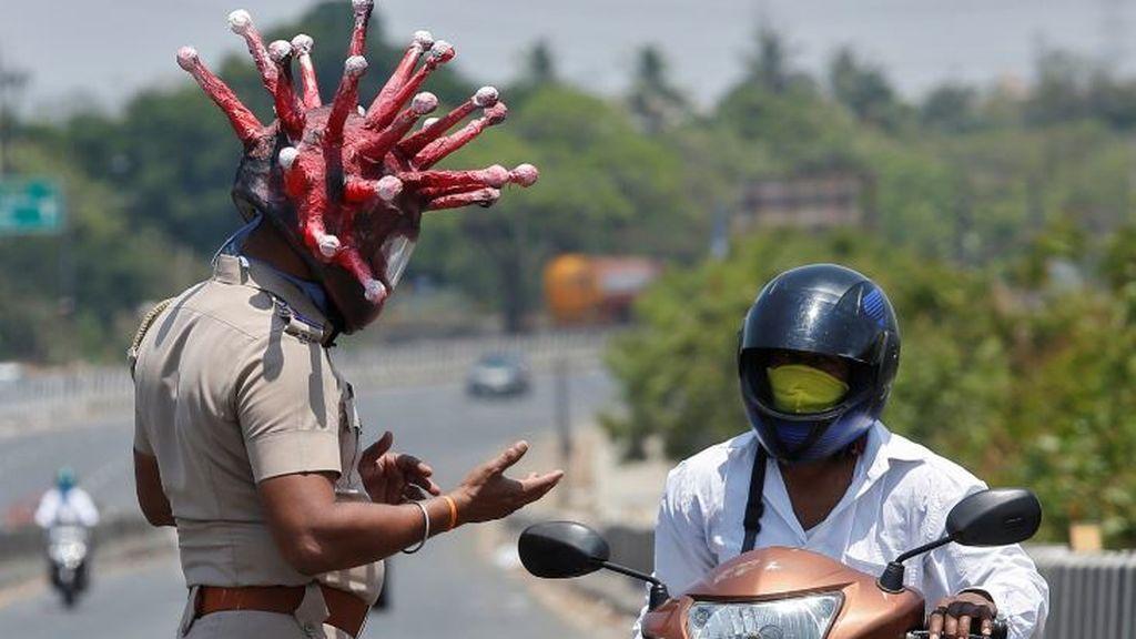 En Chennai, ciudad india, un policía con un casco que representa al coronavirus conmina a un motorista a respetar el confinamiento