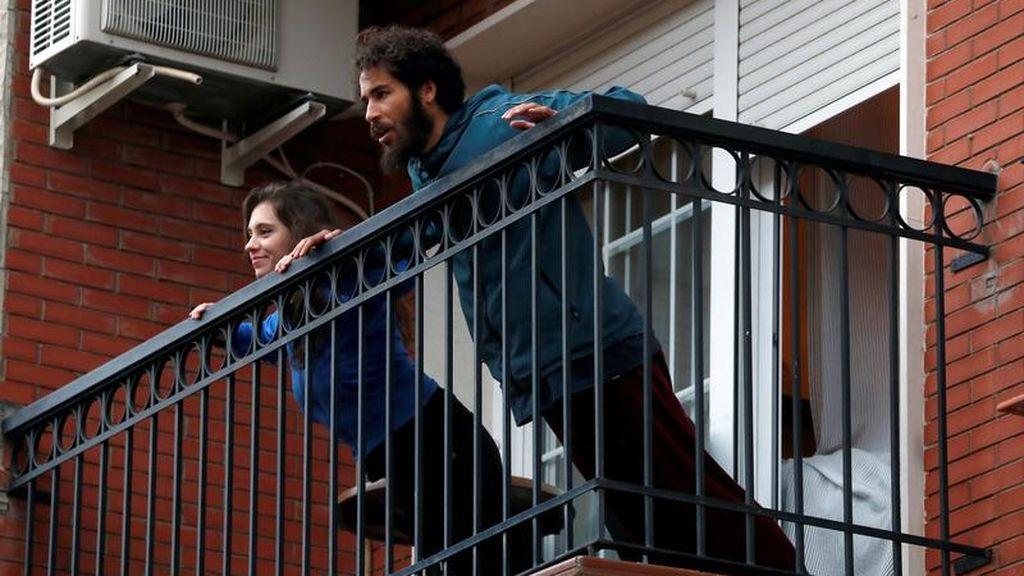 Dos personas hacen ejercicio al aire libre en su balcón