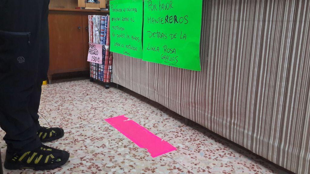 Una linea rosa marca la distancia que hay que mantener hasta el mostrador.