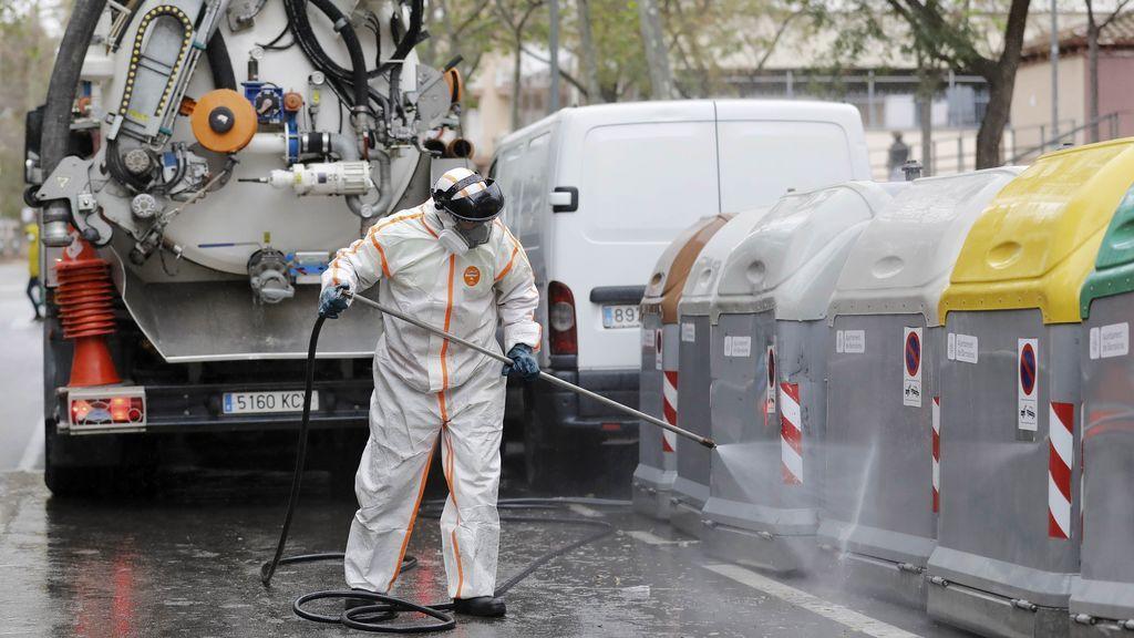 Operarios del servicio de limpieza desinfectan contenedores en Barcelona