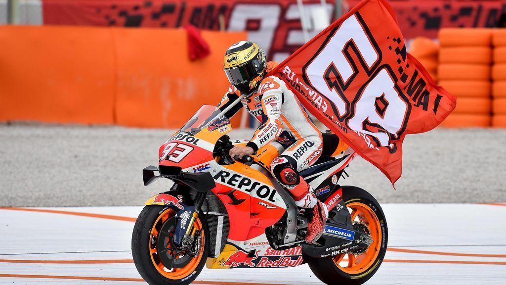 Marc Marquez celebrando una carrera llevando su bandera mientras pilota