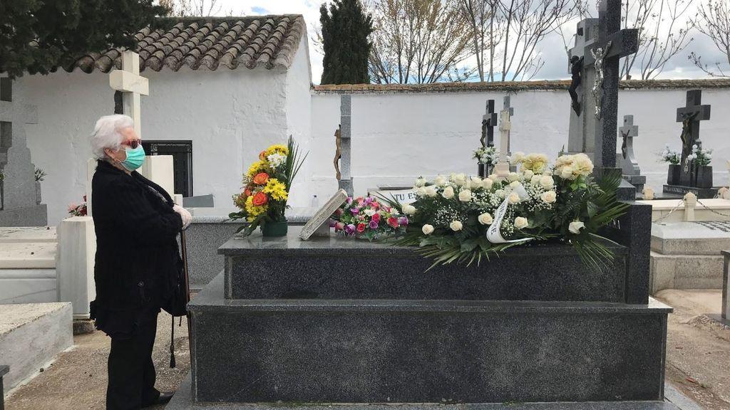 Una mujer frente a una tumba