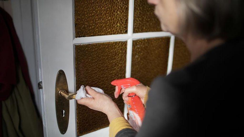 Una mujer desinfecta el pomo de una puerta