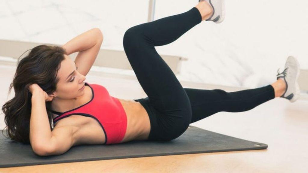 Mujer ejercitando los oblicuos en una rutina de abdominales