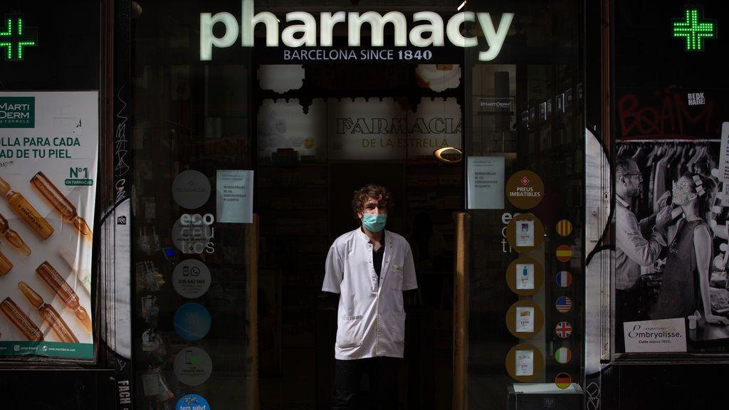 EuropaPress_2722802_farmaceutico_protegido_mascarilla_puerta_farmacia_segundo_dia_laborable