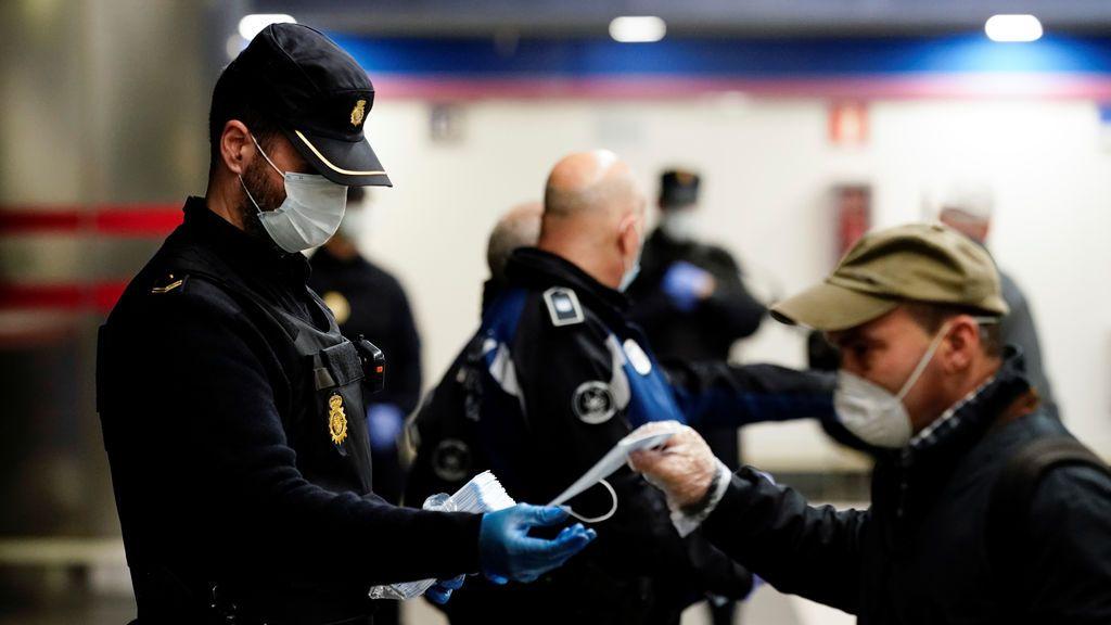 Agentes de la Policía Nacional reparten mascarillas en el transporte público