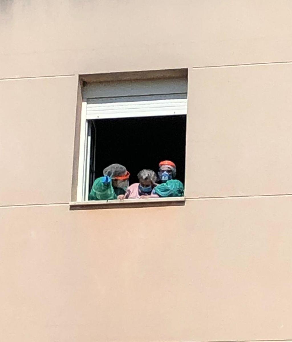 Justina saludando a su familiares desde la ventana.