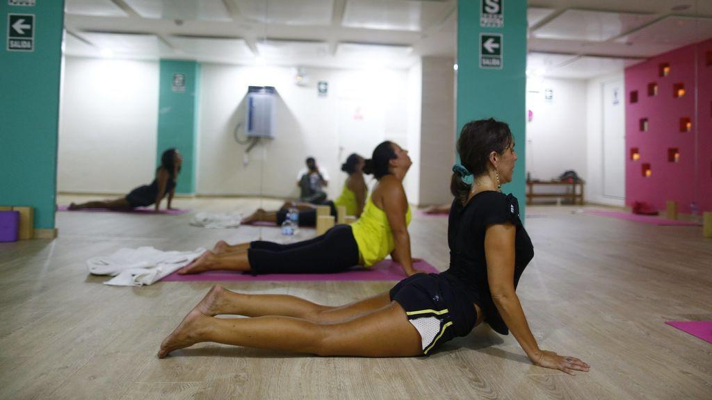 Una clase de yoga realizando la postura de la cobra