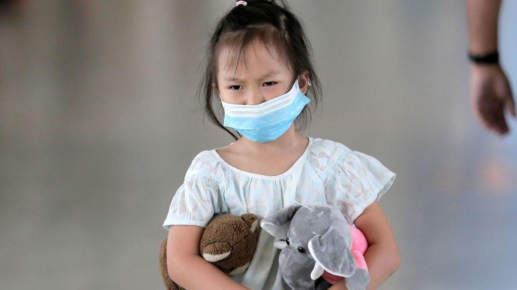 Imagen de una niña con una mascarilla de adulto