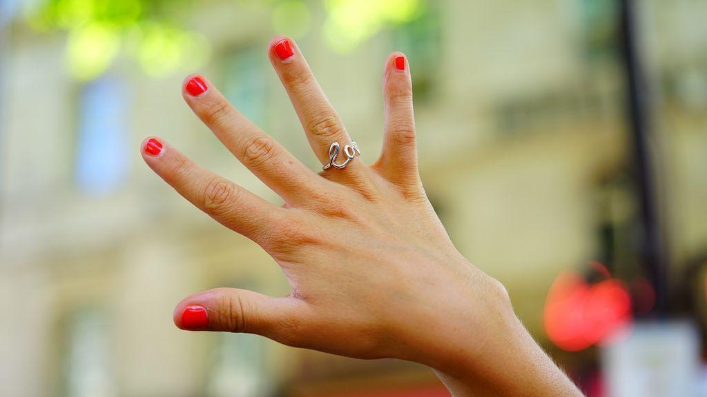 Una mano con las uñas pintadas y un anillo