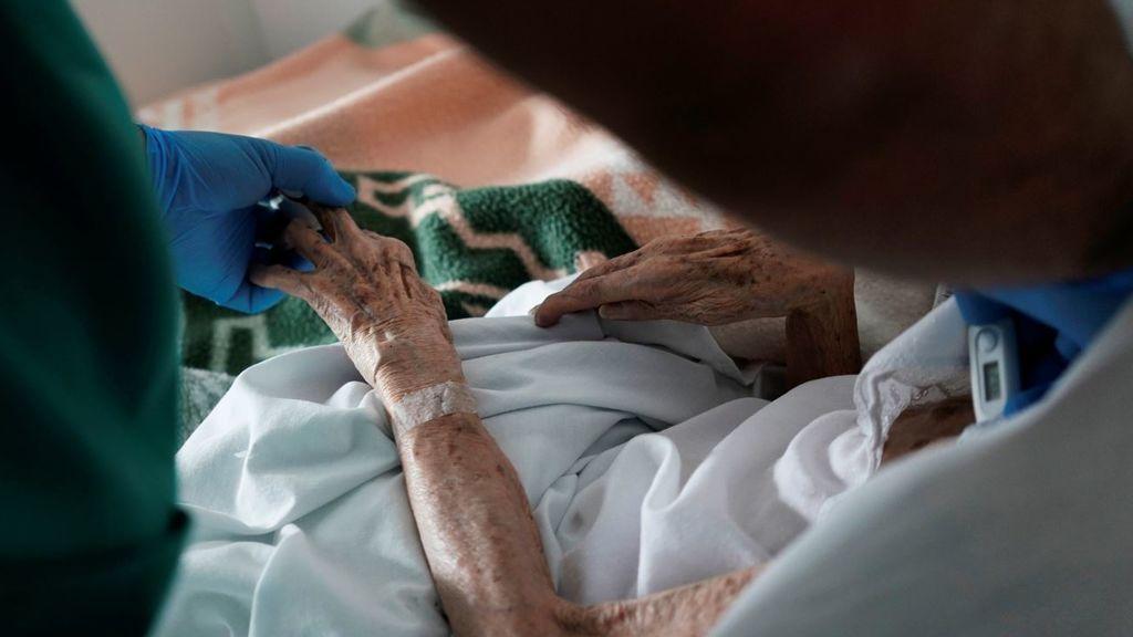 Un sanitario ayuda a un enfermo de coronavirus