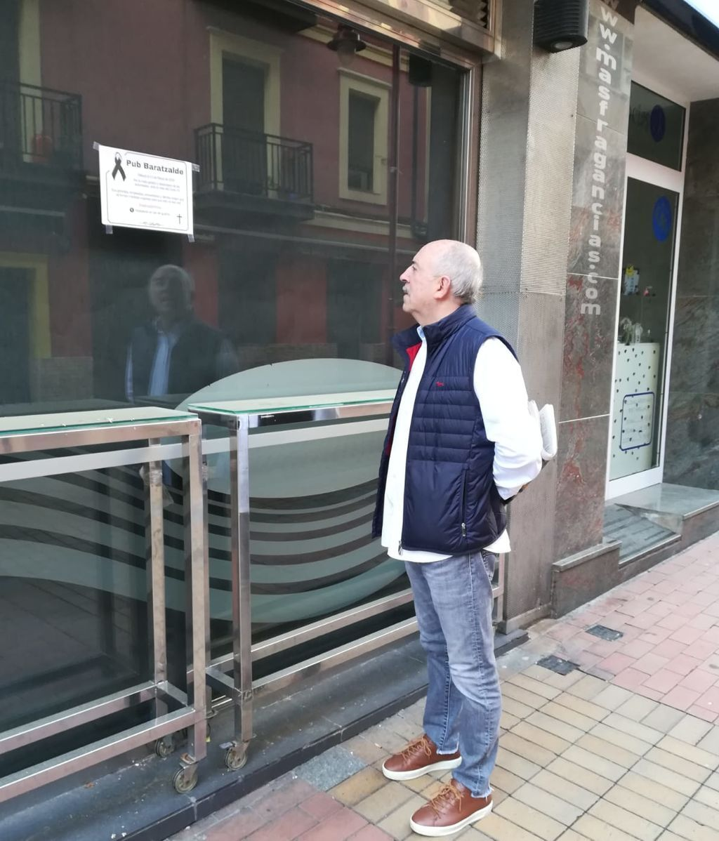 Iñaki Vallejo, mirando la esquela que ha colocado en la entrada de su local.