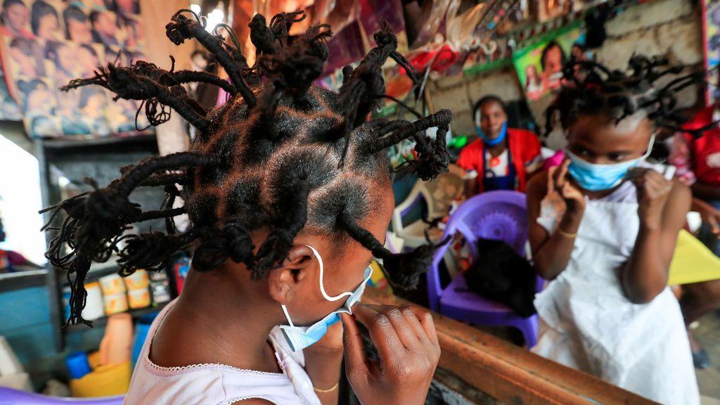 Una niña de Kibera, en Nairobi, se ajusta la mascarilla tras cambiar su look