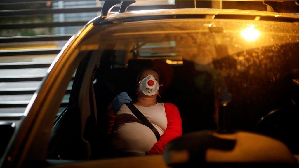 Mujer embarazada con mascarilla viajando en coche