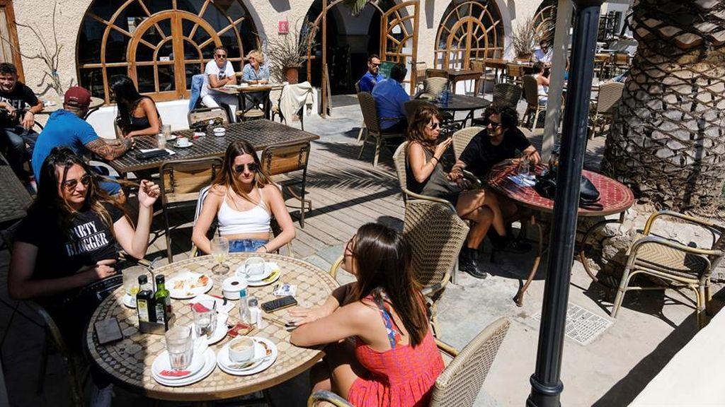 Varias personas desayunan en las terrazas de los bares de la playa de Talamanca en Ibiza