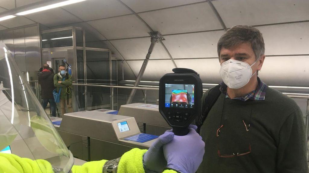 Un voluntario de la DYA toma la temperatura a un pasajero de metro bilbaíno.