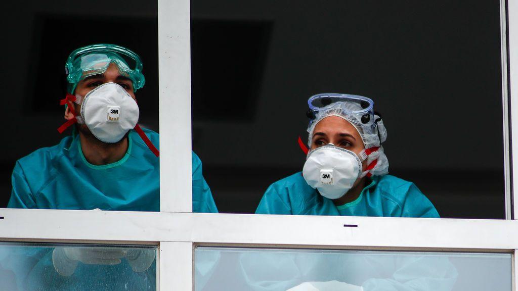EuropaPress_2861935_varios_sanitarios_proteccion_epi_mascarillas_gafas_guantes_observan_ventana