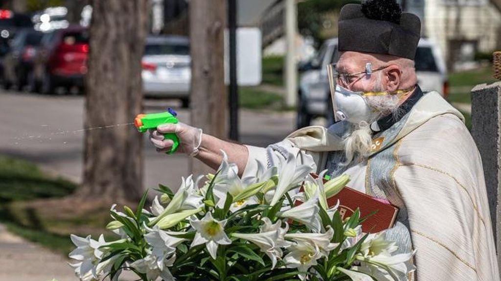 Un cura de Detroit utiliza una pistola de agua para bendecir manteniendo la distancia social