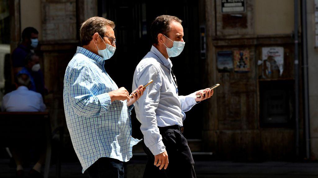 Dos hombres con mascarilla pasean por Almería