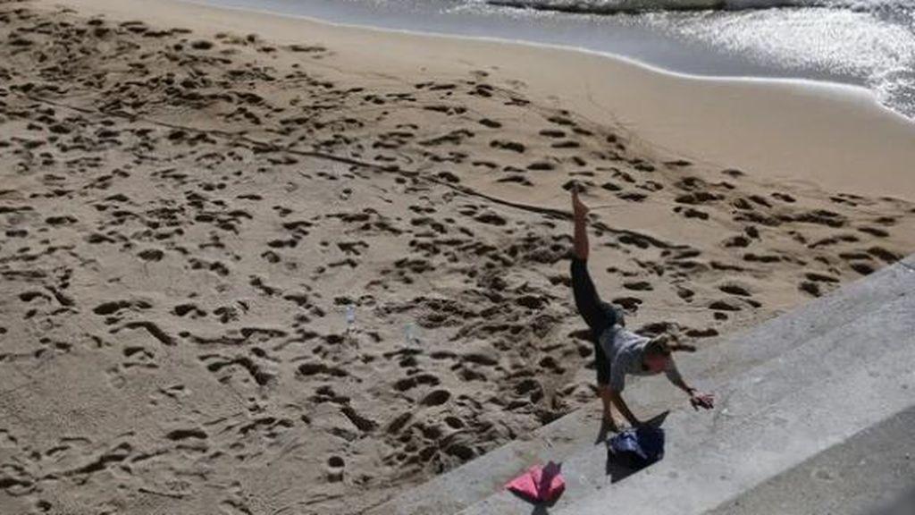 Una mujer hace ejercicios en una playa de Barcelona, una actividad autorizada en la fase 0