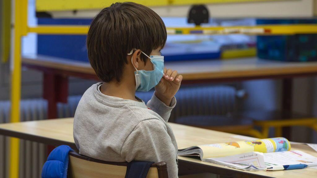 Un niño usa mascarilla en el aula de un centro escolar