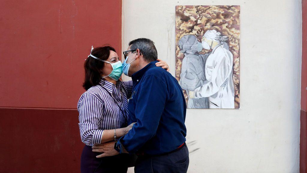 Una pareja se besa con mascarilla en Málaga