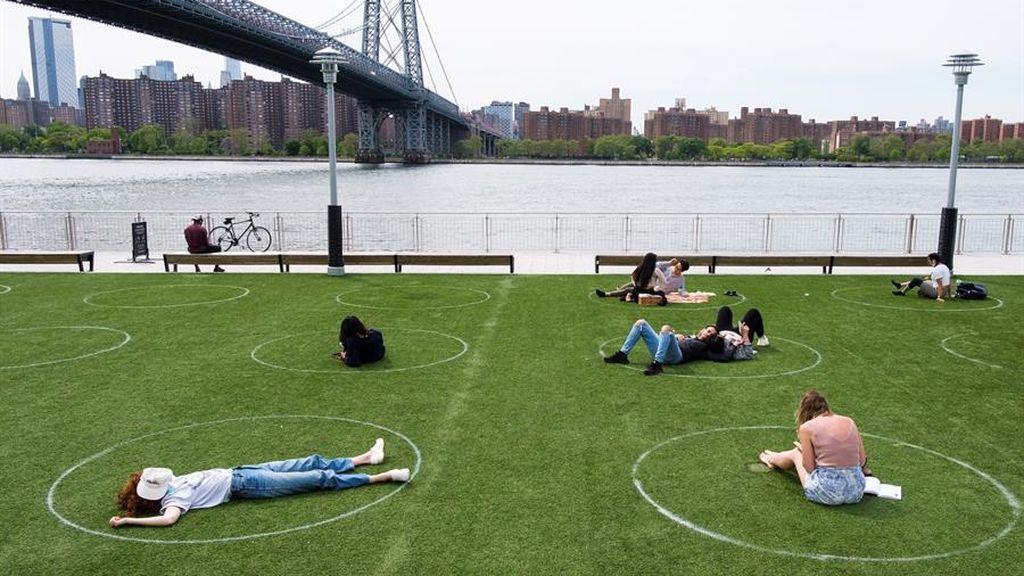 Jóvenes tumbados en un parque de Brooklyn, Nueva York, con la zonas marcadas sobre el césped para mantener la distancia social