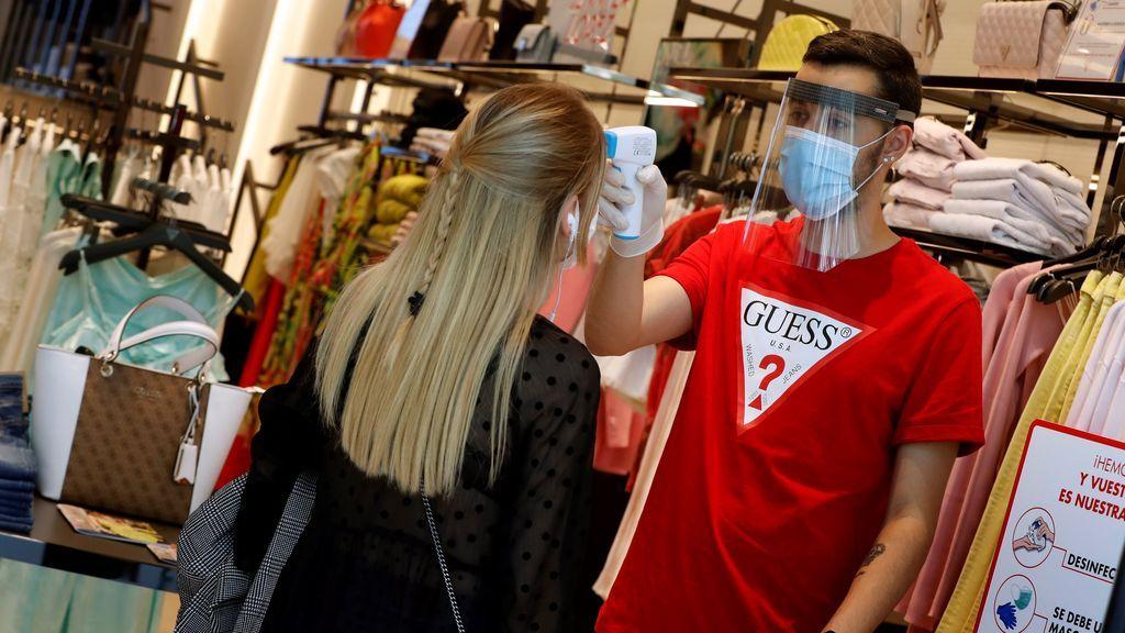 Un empleado de una tienda de ropa toma la temperatura a una clienta en Barcelona