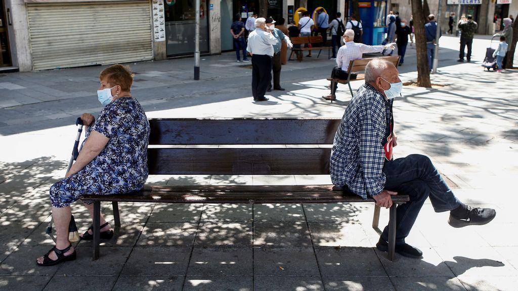 Dos personas mayores se sientan en un banco en España