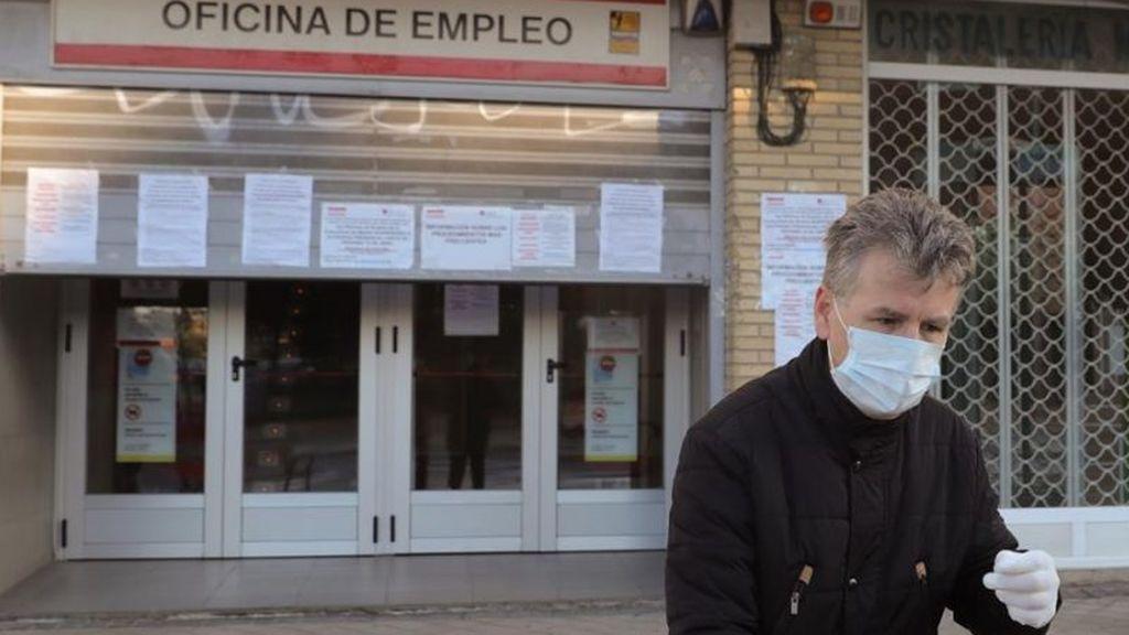 Un hombre junto a una oficina de empleo