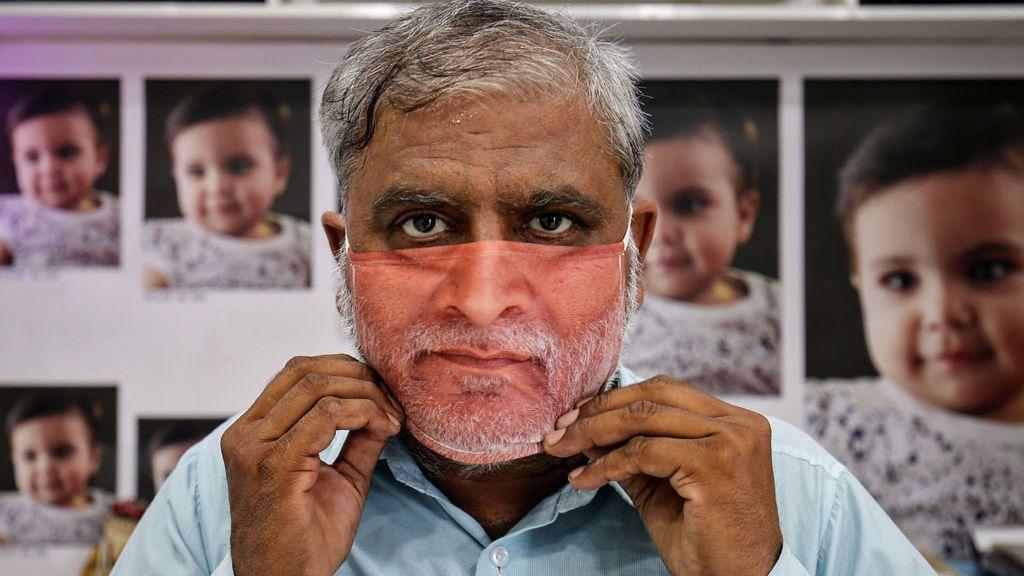 Un hombre prueba una mascarilla con su foto en Gandhinagar, India (mayo, 2020)