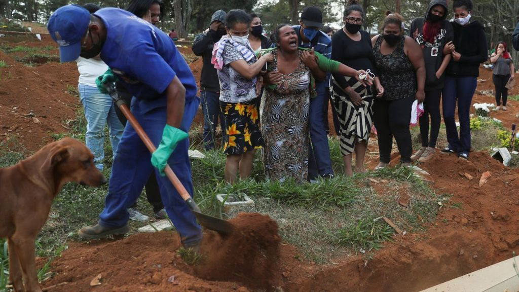 Uno de los trabajadores cubre el féretro con tierra