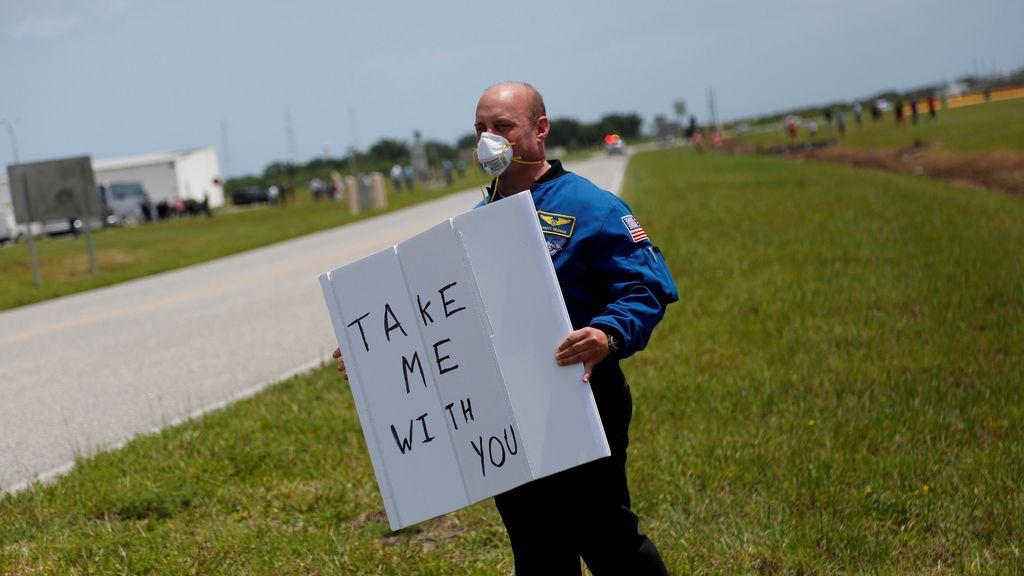 El exastronauta Garrett Reisman sostiene un cartel durante el lanzamiento de la Crew Dragon