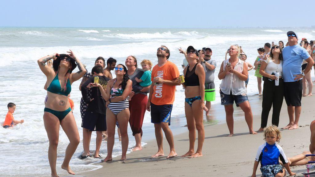 Una multitud observa desde la playa el lanzamiento exitoso de la Crew Dragon a la Estación Espacial Internacional