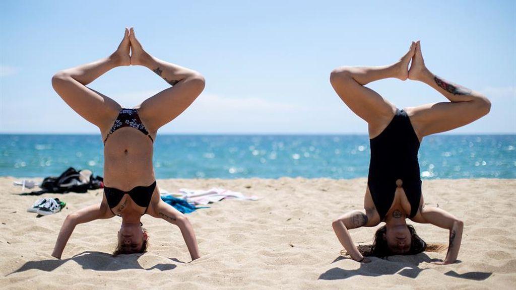 Dos mujeres hacen yoga en en la playa de la Mar Bella de Barcelona este miércoles