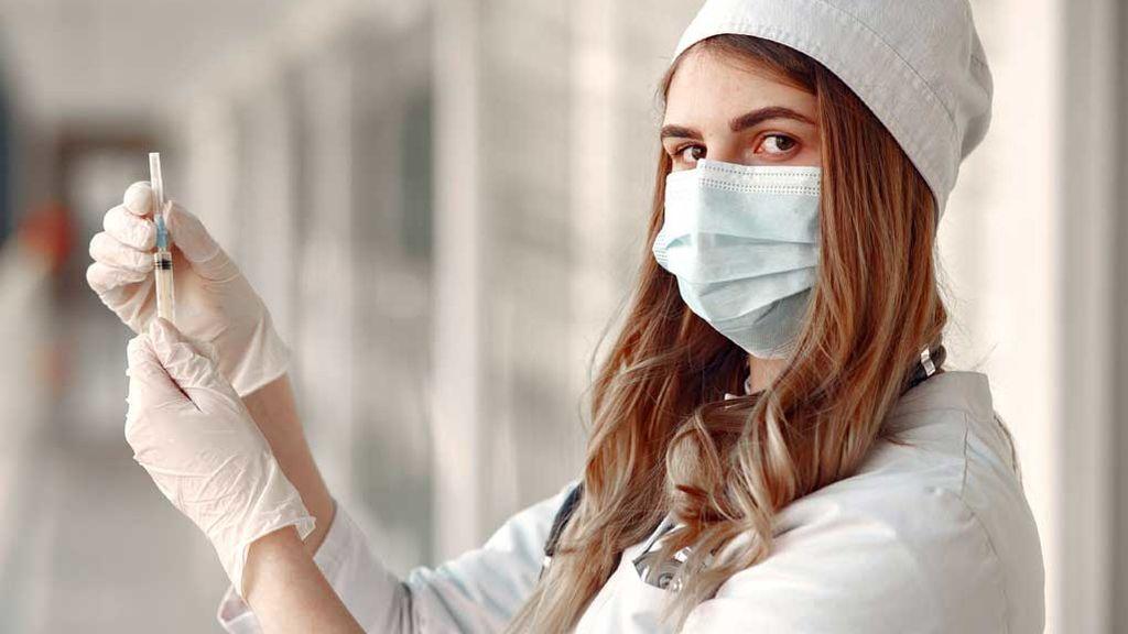 Una enfermera se dispone a poner una vacuna