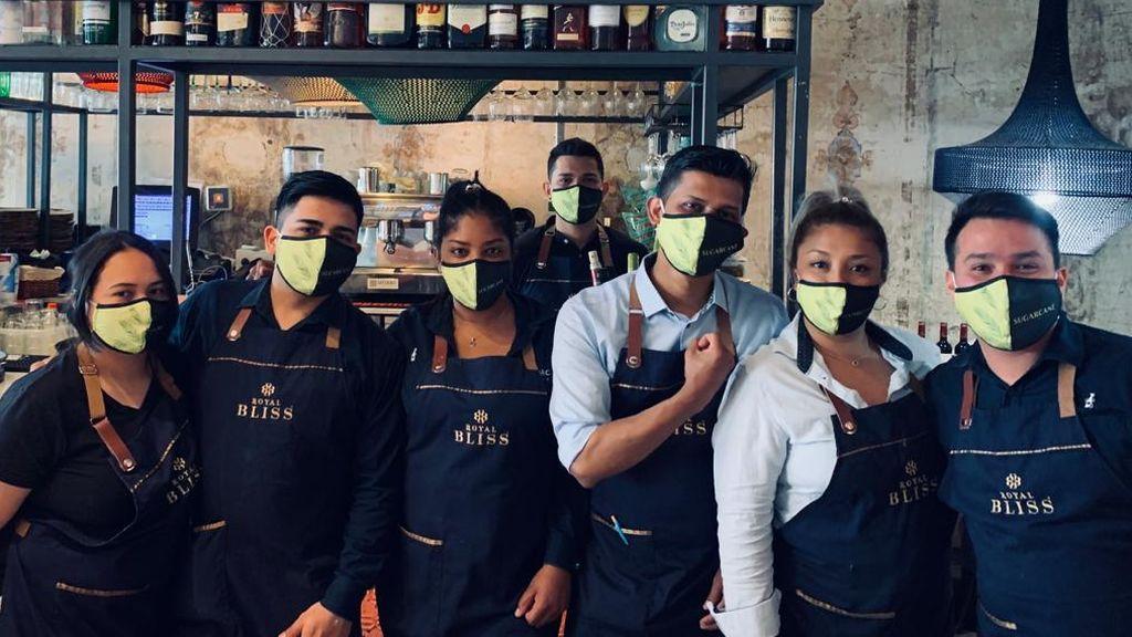Trabajadores de un restaurante con mascariilas diseñadas por esta empresa onubense.