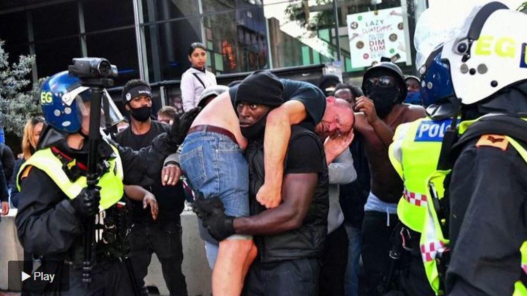 Un hombre negro rescata y carga en sus hombros a un ultraderechista herido en una manifestación en Londres